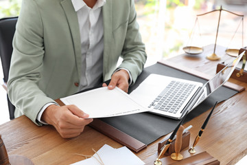 Male notary with documents and laptop at table in office, closeup