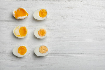 Various types of boiled eggs on white wooden background, flat lay with space for text. Cooking time