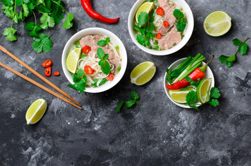 Traditional Vietnamese Soup Pho Bo with Rice Noodles, Beef and Herbs on Dark Background