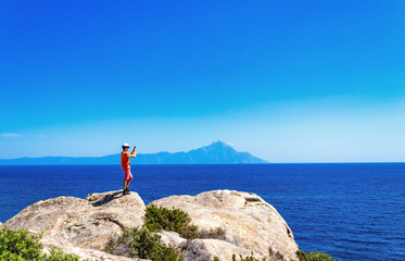 teen boy photographing sea and mountains standing on cliff