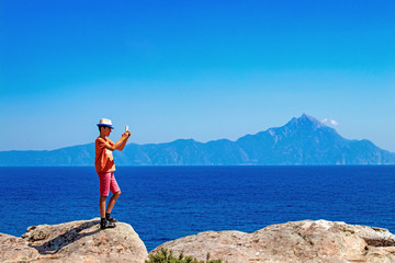 teen boy makes selfie standing on a cliff, Greece, Athos