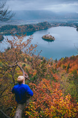 Young boy sitting on the tree and looking at Bled Lake, Island,Church And Castle, Slovenia, Europe