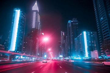 Spoed Foto op Canvas Nacht snelweg Driving a car on Sheikh Zayed Rd in Dubai at night, United Arab Emirates. Blurred motion. Duotone retro wave neon noir lights color toned