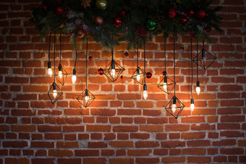 Brick wall with light bulbs and New Year's decoration