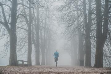 Morning run in foggy winter park. Sport active photo
