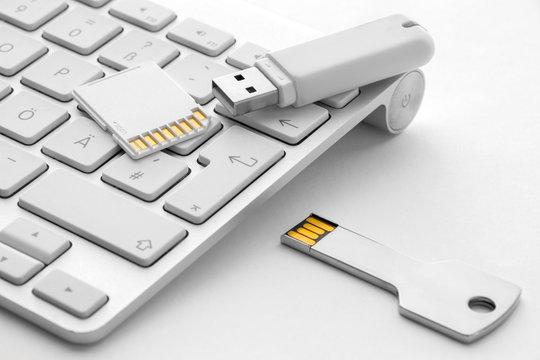 SD card USB stick and USB key on white keyboard
