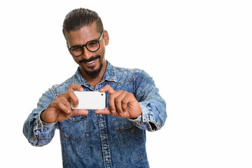 Young happy Indian man taking picture with mobile phone