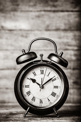classic alarm clock with bell on wooden table. Photo in black and white image style.
