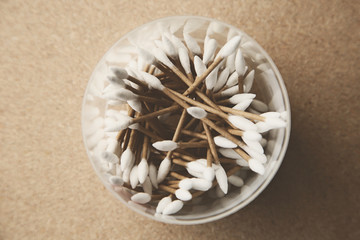 A plastic container with cotton ear swabs inside isolated on a wooden table top.