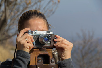 A women takes pictures with the old Soviet rangefinder film camera FED
