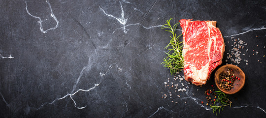 Photo sur Aluminium Viande Raw Fresh Marbled Meat Beef Steak. Herbs and Seasonings on a black marble Background Rosemary Pepper and Salt Ingredients for Cooking Top View Copy space for Text