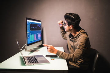 Young indian man happy victory gesture looking on display with bitcoin cryptocurrency market in dark office. Bitcoin, litecoin ethereum on PC, golden coins, operations cryptocurrency