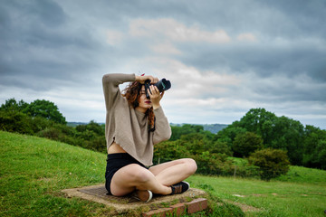 young woman photographer taking landscape photo in west midlands, UK