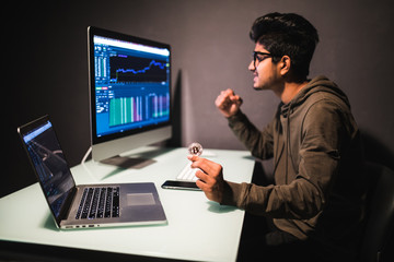 Young indian man pointed on coin looking on display with bitcoin cryptocurrency market in dark office