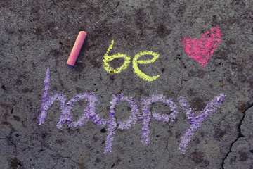 Colorful chalk drawing on asphalt: Words BE HAPPY