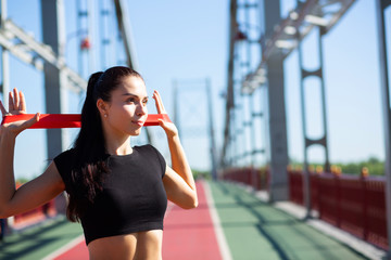 Slender sporty girl doing training with rubber resistance band on a bridge. Empty space