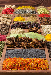 Fototapete - Spices and herbs background. Flavors from around the world. Colorful condiments for cooking tasty food. Seasonings in wooden box.