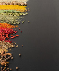 Fototapete - Colorful spice background for website  headers or food labels. Collection of herbs and herbs are scattered on black table.