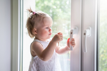 Child playing on window sill