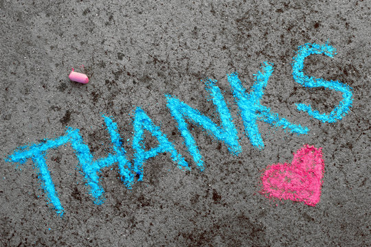 Colorful chalk drawing on asphalt: Blue word THANKS and small pink heart