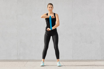 Energetic woman dressed in black top and leggings, sportshoes, stretches hands with fitness gum, prepares for competitions, isolated over grey studio background. Athletic young girl with expander.