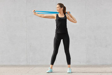 Shot of sporty young woman dressed in black clothes, stretches hands with fitness gum, wants to have muscles, has good flexibility, poses against grey background. People and motivation concept