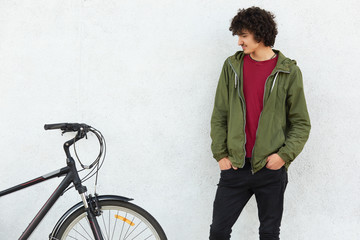 Photo of attractive hipster with curly dark hair, wears green jacket and black trousers, keeps hands in pocket, looks at his bike after ride, isolated over white concrete background. Youth concept