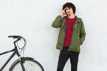 Pensive man keeps finger on temples, tries to recollect something in mind, dressed in green jacket, stands near bicycle, isolated over white concrete background. People, youth and transport concept