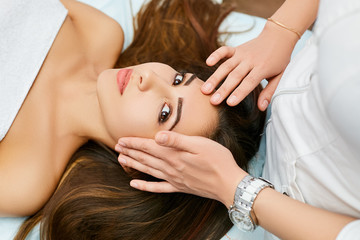 Young brunette during a facial massage in a beauty salon