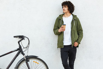 Photo of handsome youngster with curly bushy hair, dressed in white t shirt, trousers, green anorak, keeps hand in pocket, concentrated aside, drinks takeaway coffee, rides on sport bicycle.