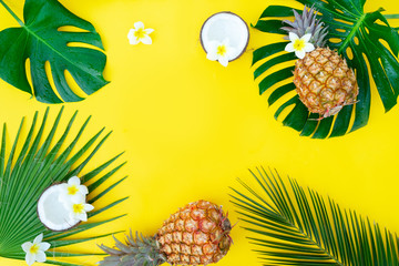 Summer flat lay frame with fresh tropical green leaves, coco and pineapples frame on yellow background