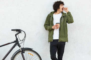 Image of handsome male yawns as wants to sleep, keeps hands near mouth, drinks strong hot coffee to feel refreshed, being tired after riding sports bicycle, isolated over white concrete wall.