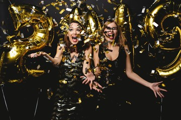 Beautiful Women Celebrating New Year. Happy Gorgeous Girls In Stylish Sexy Party Dresses Holding Gold 2019 Balloons, Having Fun At New Year's Eve Party. Holiday Celebration. High Quality Image