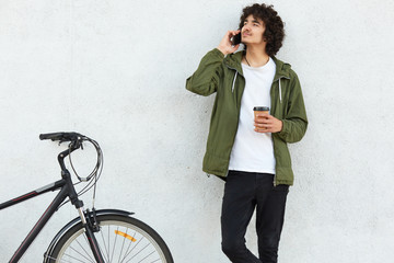 Shot of concentrated male youngster speaks via cell phone with girlfriend, tells about his bike travel, holds takeaway coffee, poses against white concrete wall. Youth, technology, lifestyle concept