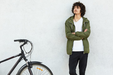Self confident focused man has curly hairstyle, keeps arms folded, dressed in jacket and jeans, looks thoughtfully aside, rides bicycle, models against white background. Active lifestyle concept