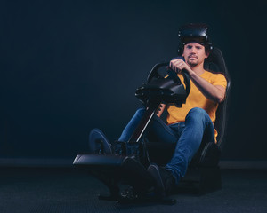 Man dressed in yellow shirt and jeans in VR headset sitting on a car racing simulator