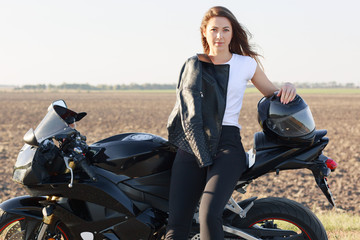 Horizontal shot of attractive motorrcyclist leans at motorrbike, keeps hand on helmet, stands near bike, has leather jacket on herself, models outdoor. People, high speed and destination concept