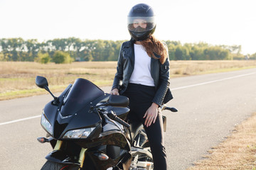 Street style concept. Active professional rider wears helmet, black leather jacket, poses on motorrbike at road, enjoys high speed, ready to cover long distance and have trip. Horizontal shot