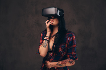 Tattooed girl wearing a red unbuttoned checked shirt wearing a VR headset.