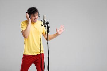 Portrait of handsome man in headphones sing on studio microphone on grey background. Singer concept.