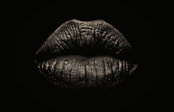 Seductive female full lips on black background. Fashionable and luxury lip professional make up. Dark side of human behavior. Young girl's lips.