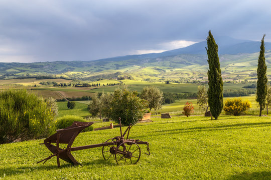 Tuscany rural landscape early in the morning, old plow in the foreground. Travel Europe, Italy.