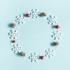 Christmas or winter composition. Wreath made of snowflakes, pine cones and red berries on pastel blue background. Christmas, winter, new year concept. Flat lay, top view, copy space
