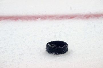 black hockey puck on ice rink. Winter sport.