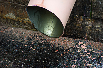 Outdoor pink drainpipe and wet asphalt is close