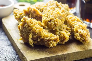 Fried chicken wings on wooden cutting board.
