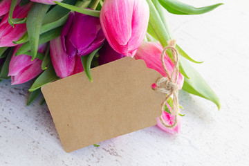Violet fresh tulip flowers on white wooden background, copy space on paper note