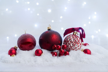 Christmas scene with snow - red balls decorations with lights in background