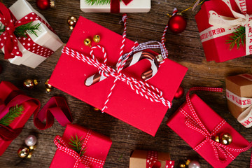 Christmas gift giving concept - christmas presents in red and white boxes on wooden table, flat lay top view scene