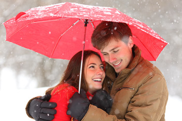Romantic couple hugging under umbrella snowing in winter